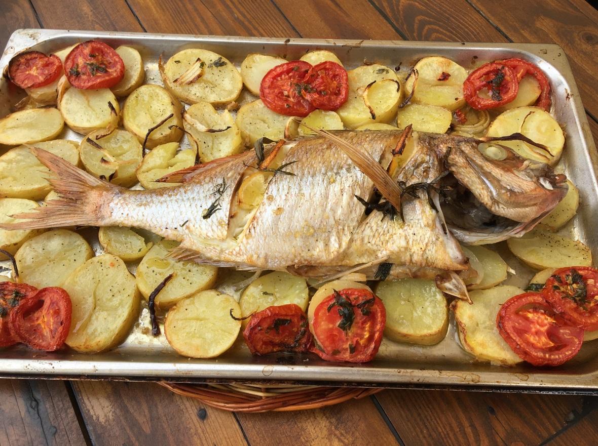 poisson cuit au four à découvert sur tomates et pommes de terre